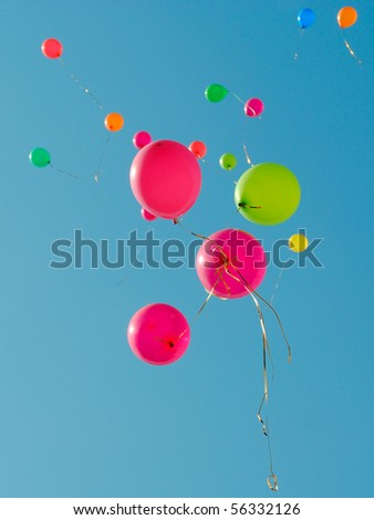 Multi-colored balloons flying up in the sky - stock photo