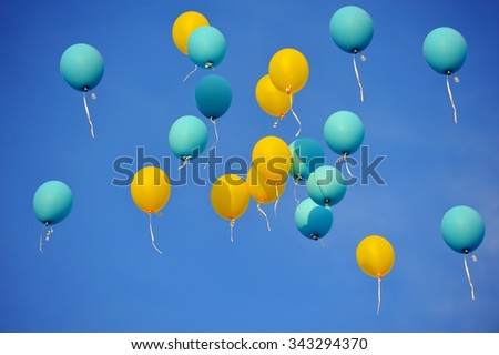 Multi-colored balloons in the blue sky - stock photo