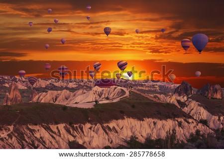 Multi-colored balloons in the sky of Cappadocia at sunrise, Turkey - stock photo