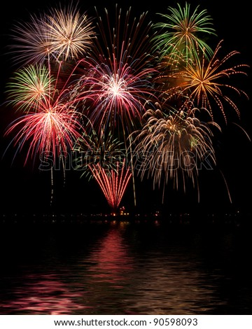 Multi-colored bursts of fireworks shining on water