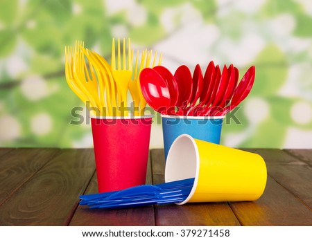 Multi-colored disposable plastic cups, forks, spoons on green abstract background - stock photo
