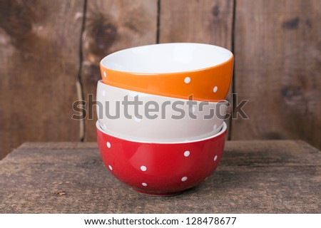 Multi colored empty big polka dot bowls: red, beige and orange