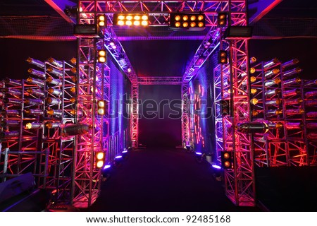 Multi-colored illuminated way with grid to boxing ring inside fight club; many lights - stock photo