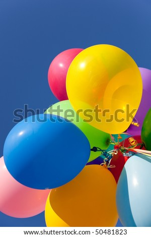 Multi colored including blue, yellow, red, pink, orange and green balloons with a sky blue background