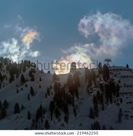 Multi-colored iridescent clouds at sunrise over of a valley of the Zillertal - Mayrhofen, Austria - stock photo