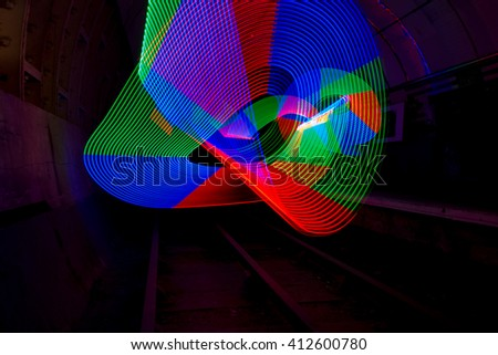Multi-colored LED light used to create a pattern in a dark tunnel - stock photo