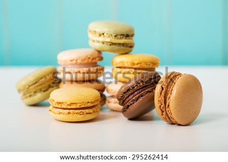Multi-colored macarons on pastel blue wooden background - stock photo