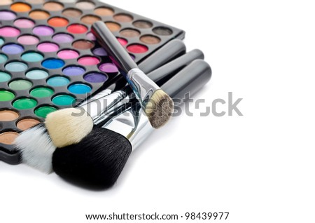 Multi colored make-up and brushes isolated on white