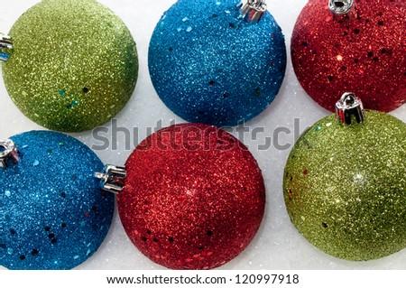 multi colored ornaments lay in the snow - stock photo
