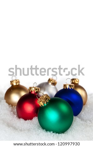multi colored ornaments laying in the snow - stock photo