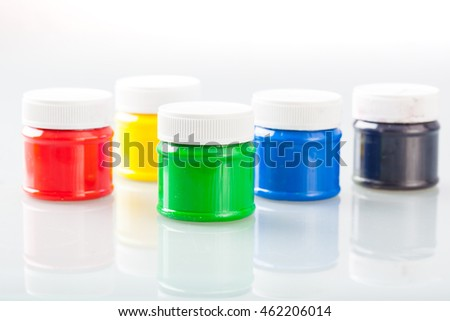 Multi colored paint bottles and caps on white background with reflection