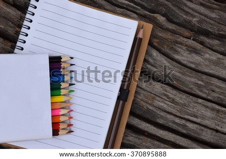 Multi colored pencils and notebook on the old wood texture.