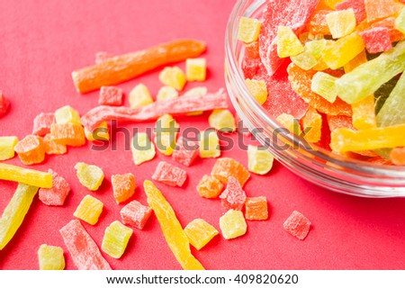 multi-colored pieces of dried pineapple in a glass bowl and near bowl on a red background