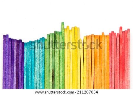 multi colored popsicle craft sticks lined up on edge over white.