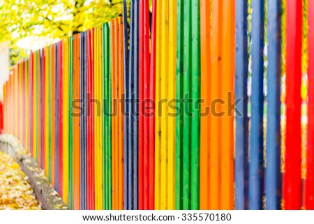 Multi colored rainbow wooden fence in autumn, garden background, soft focus, shallow depth of field