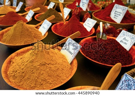 Multi-colored tasty spices with plates on which are written names of herbs and plants. - stock photo