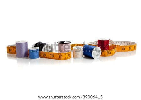Multi colored thread with a tape measure on a white background with copy space - stock photo