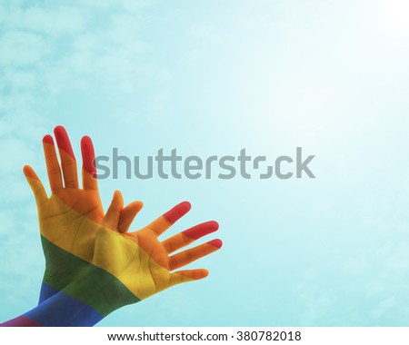 Multi-colour rainbow flag color pattern overlay on human hand in butterfly shape upwards against vintage retro style sky cloud sunlight effect: Zero discrimination day campaign symbolic concept - stock photo