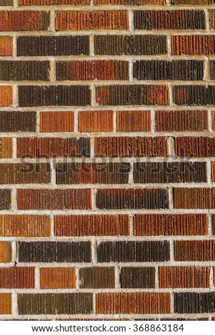 Multi coloured brick wall background and texture. Different bricks can be seen with groves and cement between them,