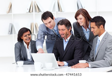 Multi-cultural business team looking at a laptop in the office - stock photo