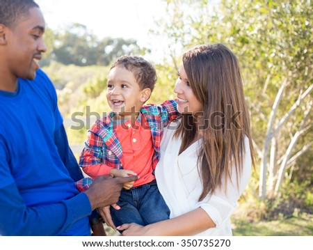 Multi cultural family together at the park - stock photo