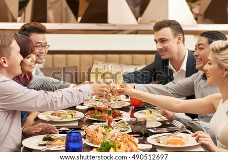 Multi-cultural group of friends clinking glasses at dinner
