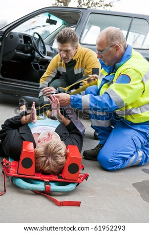 Multi-disciplinary medical team with a fireman and a paramedic, kneeling around a stretcher, and strapping an injured woman down - stock photo