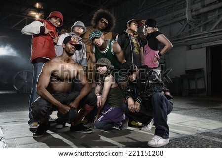 Multi-ethnic breakdancers posing in warehouse - stock photo
