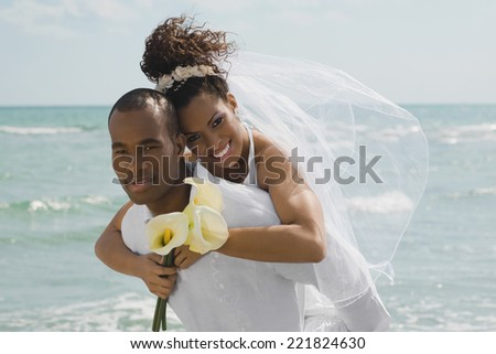 Multi-ethnic bride and groom hugging at beach - stock photo