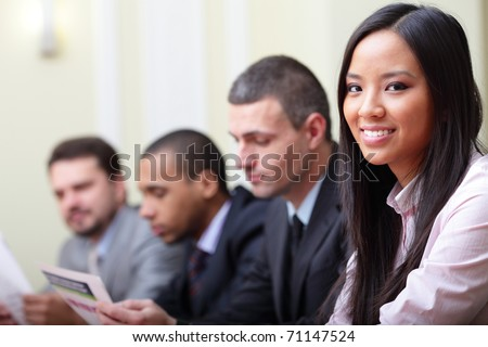 Multi ethnic business executives working with documents. Focus on woman - stock photo