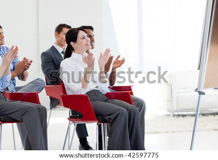 Multi-ethnic business people clapping at the end of a conference in the office - stock photo
