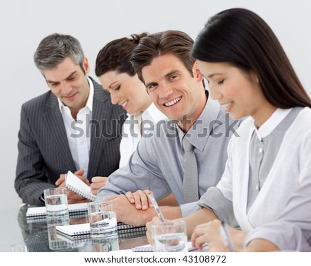 Multi-ethnic business people taking notes at a presentation in the office