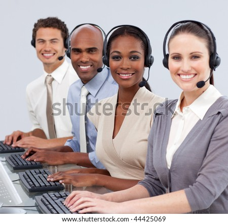 Multi-ethnic business people with headset on smiling at the camera in a call center