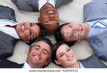 Multi-ethnic business team lying on the floor with heads together. Business concept.