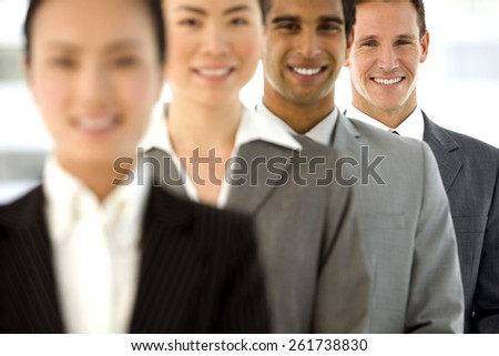 Multi ethnic business team standing in a row. Selective focus on background