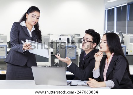 Multi ethnic business team using digital tablet to discuss business project in the office - stock photo