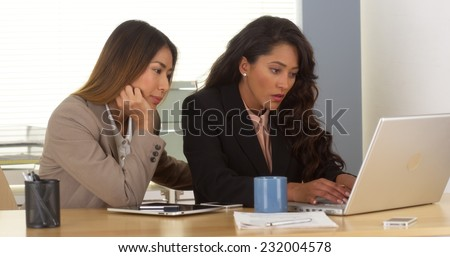 Multi-ethnic business team working on laptop - stock photo