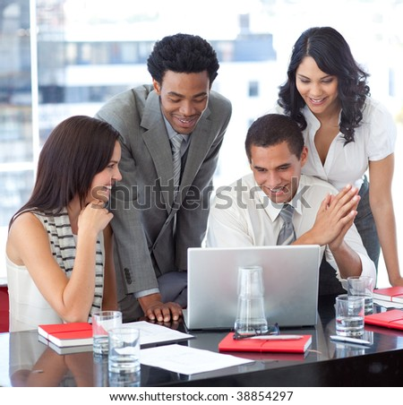 Multi-ethnic business team working together with a laptop in office - stock photo