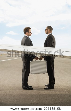 Multi-ethnic businessmen exchanging briefcase