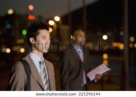 Multi-ethnic businessmen outdoors at night - stock photo