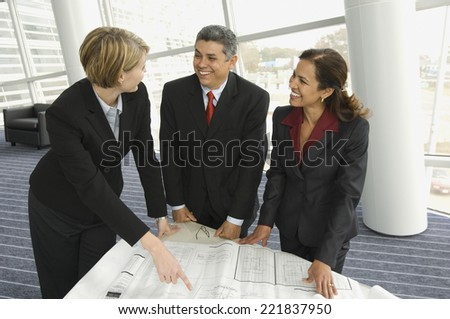 Multi-ethnic businesspeople discussing blueprints - stock photo