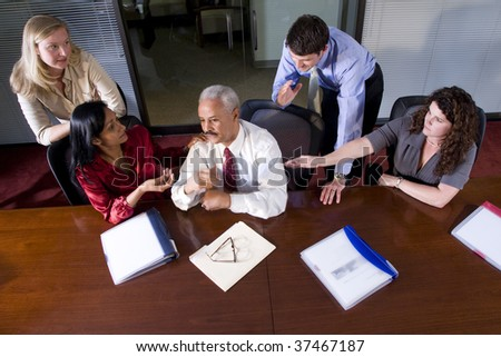 Multi-ethnic businesspeople meeting at table in boardroom - stock photo