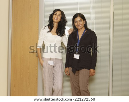 Multi-ethnic businesswoman wearing ID badges - stock photo