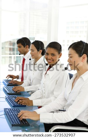 Multi ethnic call center operators. Selective focus on the Afro American woman.