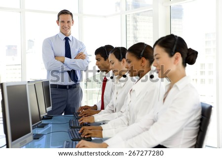 Multi-ethnic Call Center people at work with manager standing in the background - stock photo
