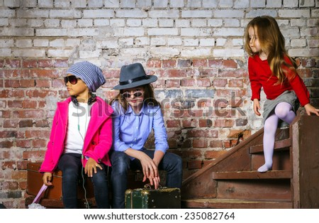 Multi-ethnic children group portrait in studio on brick-wall background - stock photo