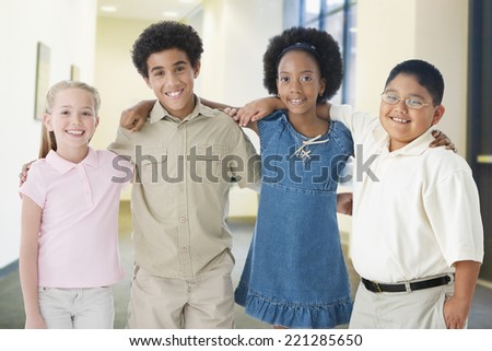 Multi-ethnic children standing arm in arm - stock photo