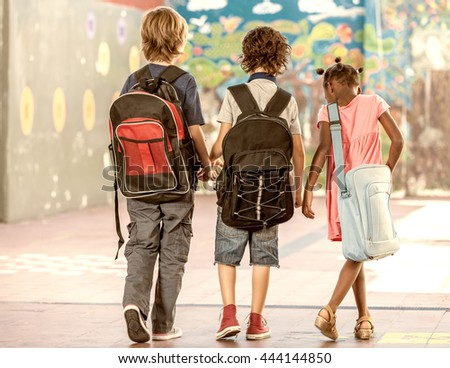 Multi ethnic classmates walking in schoolyard, seen from behind. - stock photo
