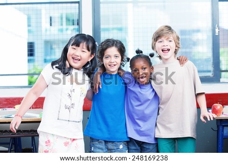 Multi ethnic classroom. Afro american, asian and caucasian primary school kids happy smiling. - stock photo