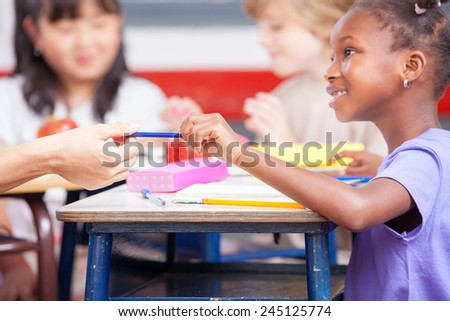 Multi ethnic classroom concept. Child handing pencil to teacher. - stock photo